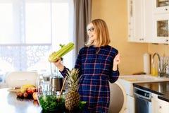Mulher gravida nova feliz que canta com aipo na cozinha imagem de stock