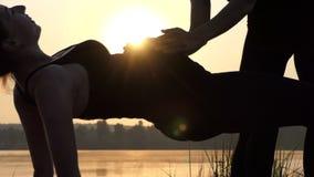 A mulher gravida nova mantém sua barriga acima, fazendo a ioga, no por do sol em 4k filme