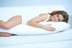 Mulher gravida nova que coloca no sofá Foto de Stock Royalty Free