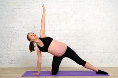 A mulher gravida nova que faz o esticão exercita na esteira da ioga Imagens de Stock Royalty Free