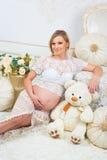 Mulher gravida nova que senta-se perto do sofá branco com urso de peluche Imagens de Stock Royalty Free