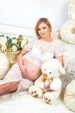 Mulher gravida nova que senta-se perto do sofá branco com urso de peluche imagens de stock