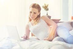 Mulher gravida positiva que encontra-se na cama Imagem de Stock Royalty Free