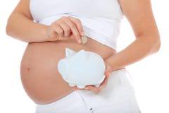 A mulher gravida põr o dinheiro no banco piggy Foto de Stock