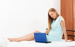 Mulher gravida que acorda com portátil azul fotografia de stock