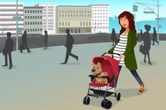 Mulher gravida que anda com seu cão e um carrinho de criança na cidade Foto de Stock Royalty Free