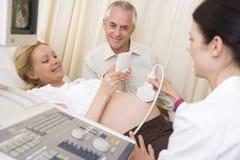 Mulher gravida que começ o ultra-som com marido Imagens de Stock Royalty Free