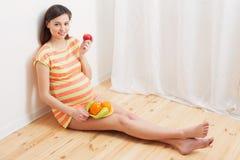 Mulher gravida que come frutos Imagens de Stock
