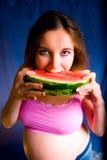 Mulher gravida que come a melancia Retrato da mulher gravida feliz que come a melancia saboroso doce em casa, comer saudável imagem de stock