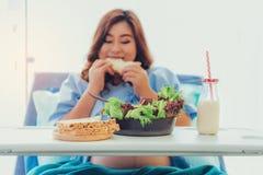 Mulher gravida que come o pão, leite, frutas e legumes, de r imagens de stock royalty free