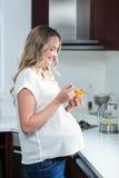 Mulher gravida que come a salada de frutos Imagem de Stock Royalty Free