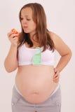 Mulher gravida que come uma maçã. Foto de Stock Royalty Free