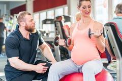 Mulher gravida que dá certo com o instrutor pessoal no gym imagem de stock