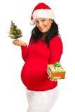 Mulher gravida que dá o presente do Xmas Foto de Stock Royalty Free