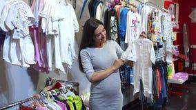 Mulher gravida que escolhe a roupa do bebê no bebê e na loja da maternidade vídeos de arquivo