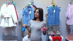 Mulher gravida que escolhe a roupa do bebê no bebê e na loja da maternidade video estoque