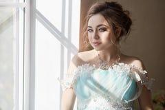 Mulher gravida que está na janela no dre bonito dos azuis celestes Foto de Stock