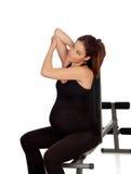 Mulher gravida que estica no gym Fotos de Stock Royalty Free