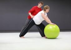 Mulher gravida que exercita com instrutor Imagem de Stock Royalty Free