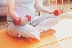 Mulher gravida que faz exercícios com pesos Fotografia de Stock