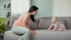 Mulher gravida que faz o bebê adorável rir, jogando com criança, felicidade vídeos de arquivo