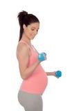 Mulher gravida que faz o exercício com pesos Foto de Stock