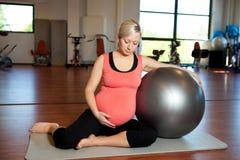 Mulher gravida que faz o exercício do abrandamento Fotos de Stock Royalty Free