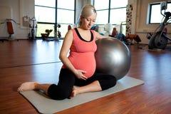 Mulher gravida que faz o exercício do abrandamento Imagem de Stock