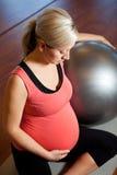Mulher gravida que faz o exercício do abrandamento Foto de Stock Royalty Free