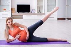 A mulher gravida que faz o exercício do esporte em casa foto de stock