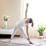 Mulher gravida que faz a pose da ioga de Utthita Trikonasana em casa Fotos de Stock Royalty Free