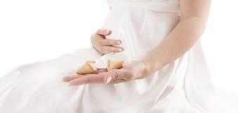Mulher gravida que guarda a cookie de fortuna Fotografia de Stock Royalty Free