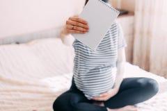 mulher gravida que guarda o caderno, papéis para notas, espaço da cópia fotos de stock royalty free