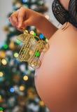Mulher gravida que guarda o carrinho de bebê perto de sua barriga Imagens de Stock