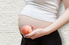 A mulher gravida que guarda o pêssego Foto de Stock