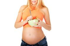 Mulher gravida que guarda uma bacia com salada Imagem de Stock
