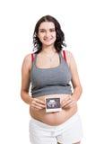 Mulher gravida que indica um ultrassom pré-natal imagem de stock