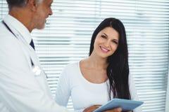 Mulher gravida que interage com o doutor fotografia de stock