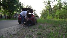 Mulher gravida que muda um pneu puncionado no carro reparo dos carros na estrada filme