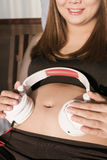 Mulher gravida que põe fones de ouvido sobre a barriga ao encontrar-se em uma cama Fotos de Stock Royalty Free