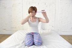 Mulher gravida que senta-se na cama que guarda o teste de gravidez positivo cor-de-rosa que cobre seus olhos com sua mão Imagens de Stock Royalty Free