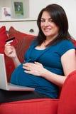 Mulher gravida que senta-se na loja de Sofa Using Credit Card To em linha Foto de Stock