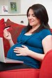 Mulher gravida que senta-se na loja de Sofa Using Credit Card To em linha Fotografia de Stock Royalty Free