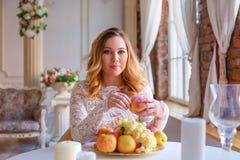 Mulher gravida que senta-se na tabela em um vestido bonito, o conceito da maternidade fotografia de stock