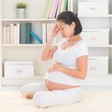 Mulher gravida que tem a dor de cabeça imagem de stock royalty free