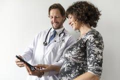 Mulher gravida que tem a monitoração fetal pelo doutor imagem de stock royalty free