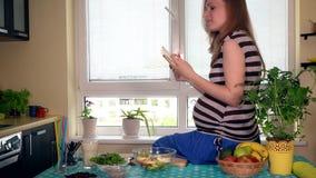 Mulher gravida que usa o tablet pc que senta-se na mesa de cozinha e que come frutos vídeos de arquivo