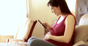 Mulher gravida que usa um app video estoque