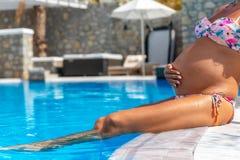 A mulher gravida relaxa pela piscina em um recurso fotografia de stock royalty free
