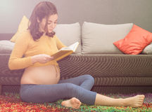 Mulher gravida saudável bonita que senta-se no tapete e que reding foto de stock